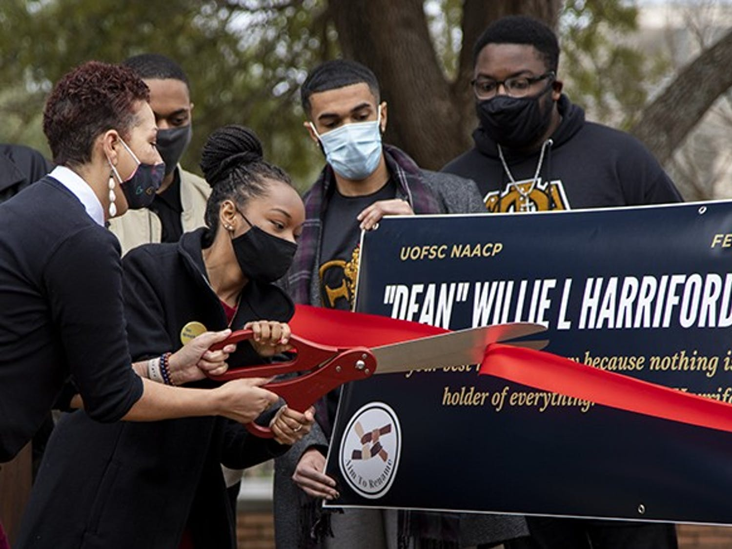 NAACP chapter President Caley Bright cuts the ribbon during the NAACP press conference.