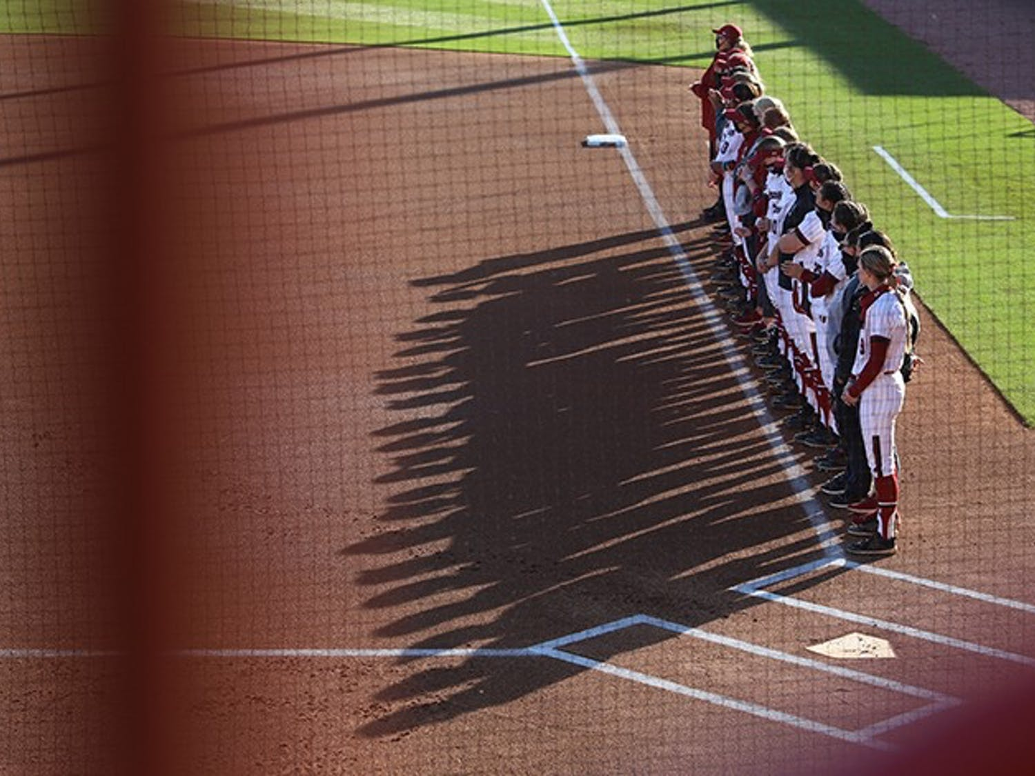 The University of South Carolina softball team stands along the diamond after the national anthem is played.