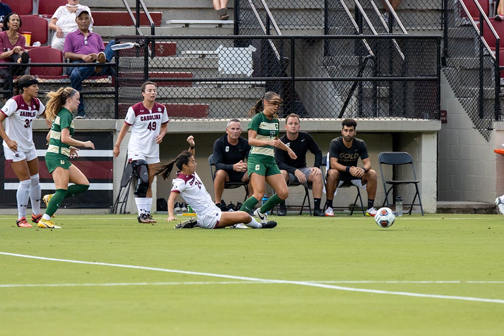 <p>Graduate student midfielder Lauren Chang slides and removes control of the ball from Charlotte player. Chang assisted a goal made by junior forward Eveleen Hahn during the first half.</p>