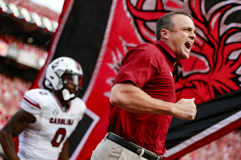<p>Head coach Shane Beamer runs out on the field before warm-ups during South Carolina's game against Georgia on Sept. 18, 2021.</p>