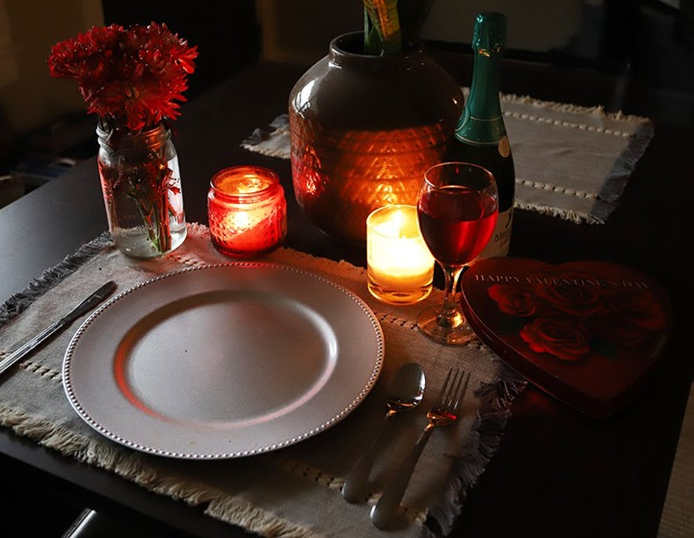 <p>A candle-lit table that is set for one with Valentine's Day paraphernalia surrounding the tableware.</p>
