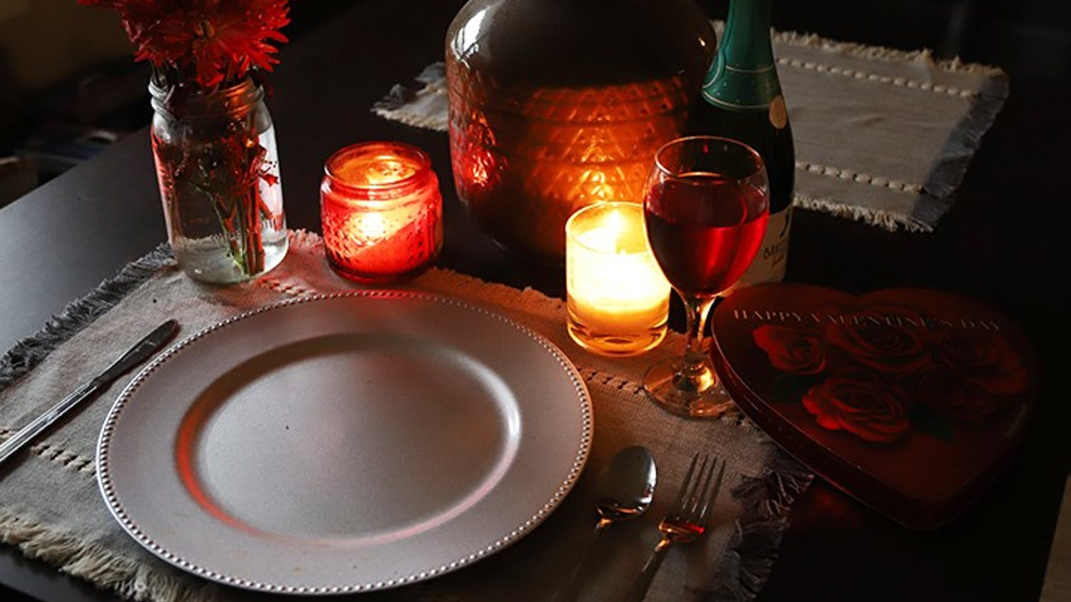 A candle-lit table that is set for one with Valentine's Day paraphernalia surrounding the tableware.