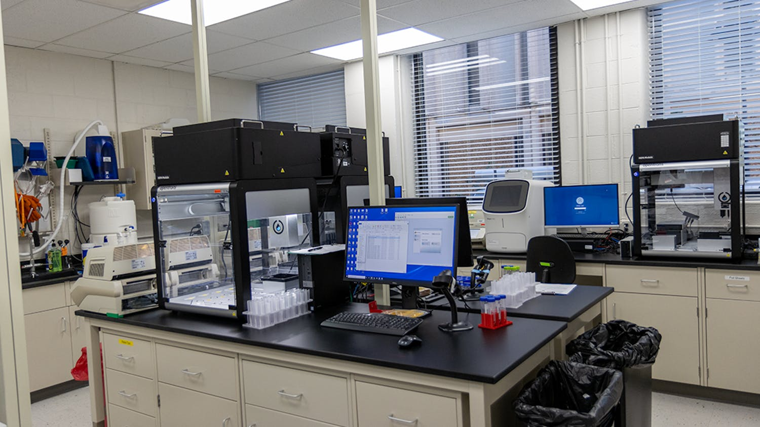 Three Opentrons OT-2 liquid handlers wait for vials to be scanned and placed inside. The recent expansion to three units allows the laboratory to process samples faster.