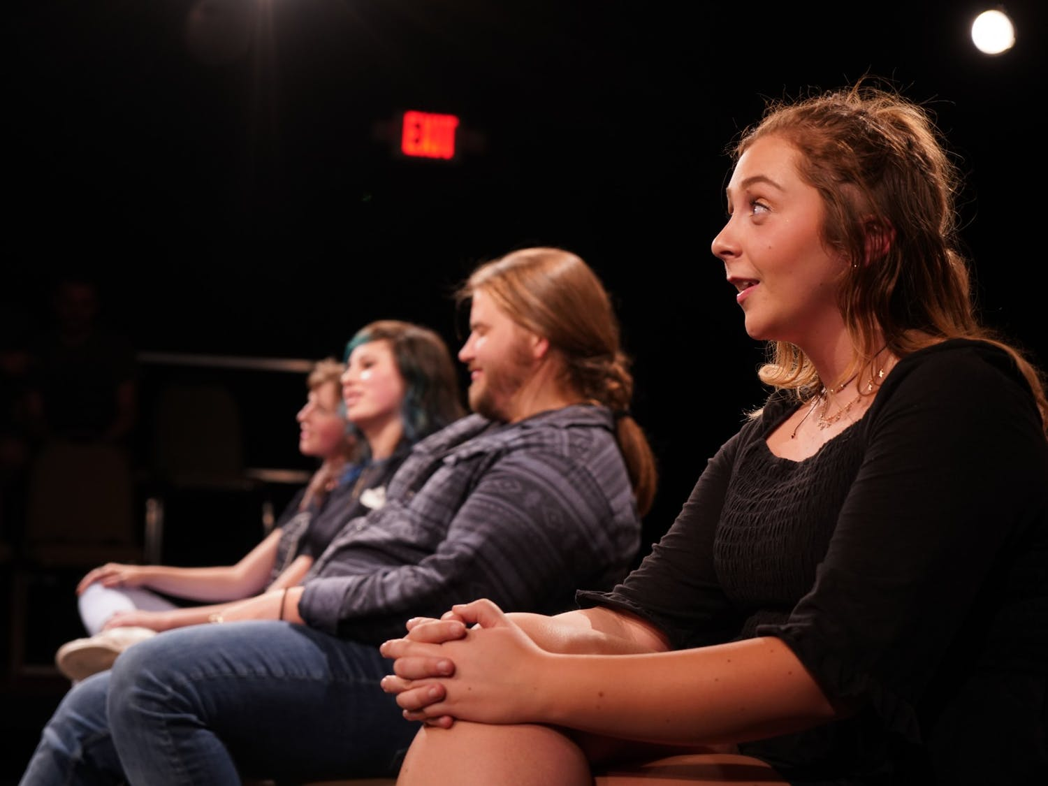 """Amber Coulter sits in a row with Casey Downs, Susanna McElveen and Cassidy Spencer during the """"Bon Voyage Prov"""" show in April 2019 by the OverReactors Improv club."""
