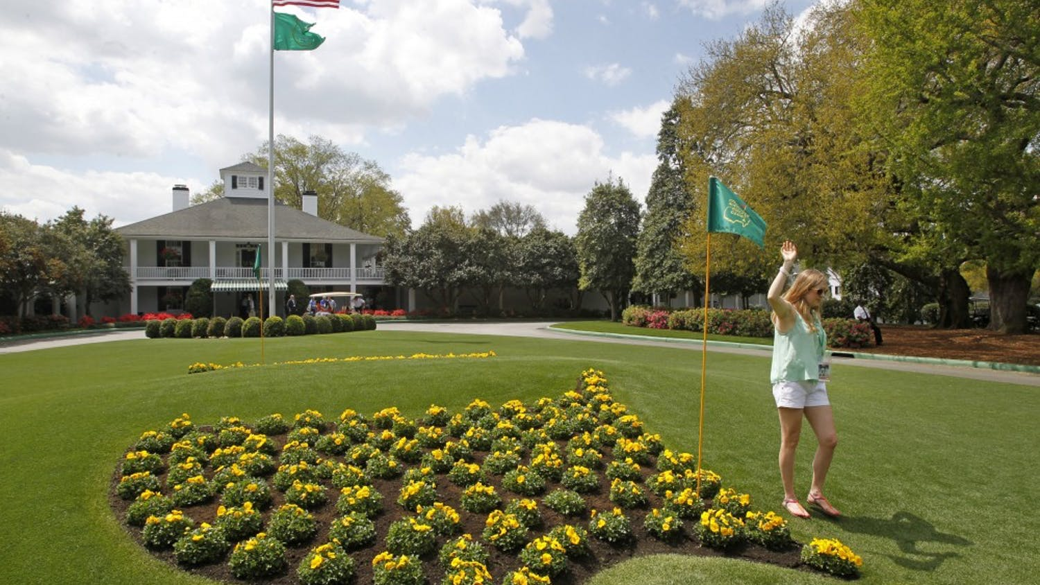 A patron poses for photos next to the Masters logo in flowers at Founders Circle in front of the Augusta National clubhouse in Augusta, Georgia, during a practice round for The Masters, Monday, April 8, 2013. (Gerry Melendez/The State/MCT)