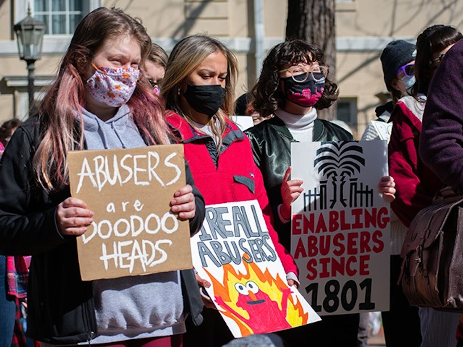 Students bring signs to protest the university's lack of response toward the numerous acts of sexual assault and violence committed by David Voros and several other staff members