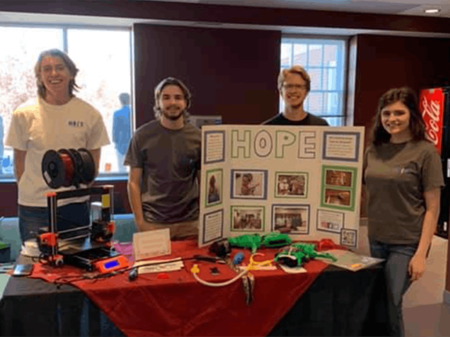 The Hands On Prosthetic Engineering organization at a table in the School of Journalism and Mass Communications. The table has an informational board, a 3D printer and examples of the organization's work.