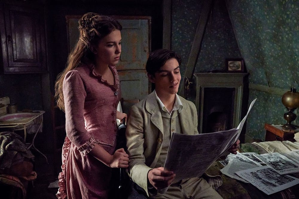 """<p>&nbsp;Enola Holmes, played by Millie Bobby Brown, and Tewkesbury, played by Louis Partridge, read a newspaper together in Netflix's new movie """"Enola Homes.""""&nbsp;</p>"""