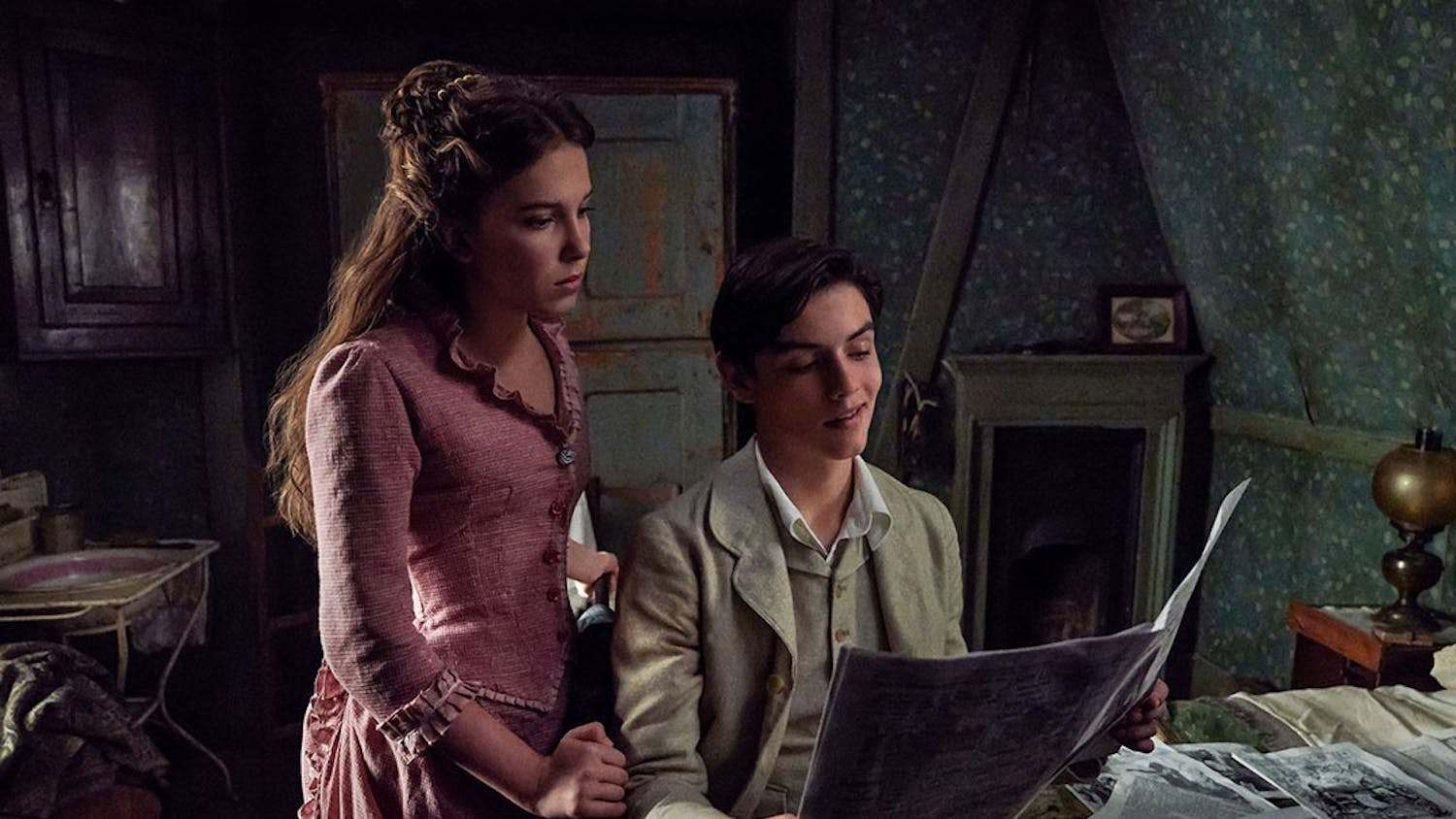 "Enola Holmes, played by Millie Bobby Brown, and Tewkesbury, played by Louis Partridge, read a newspaper together in Netflix's new movie ""Enola Homes."""