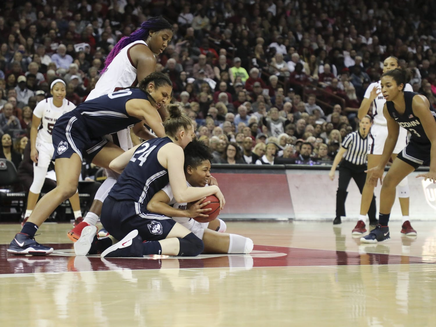 Freshman guard Zia Cooke attempts to keep the ball away from two UConn players. Cooke scored 15 points and had four rebounds against the Huskies.