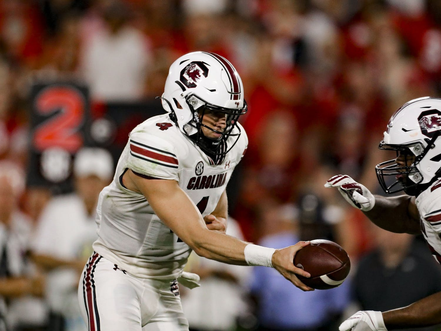Sophomore quarterback Luke Doty hands the ball off to running back Kevin Harris in South Carolina's game against Georgia on Sept. 18, 2021.