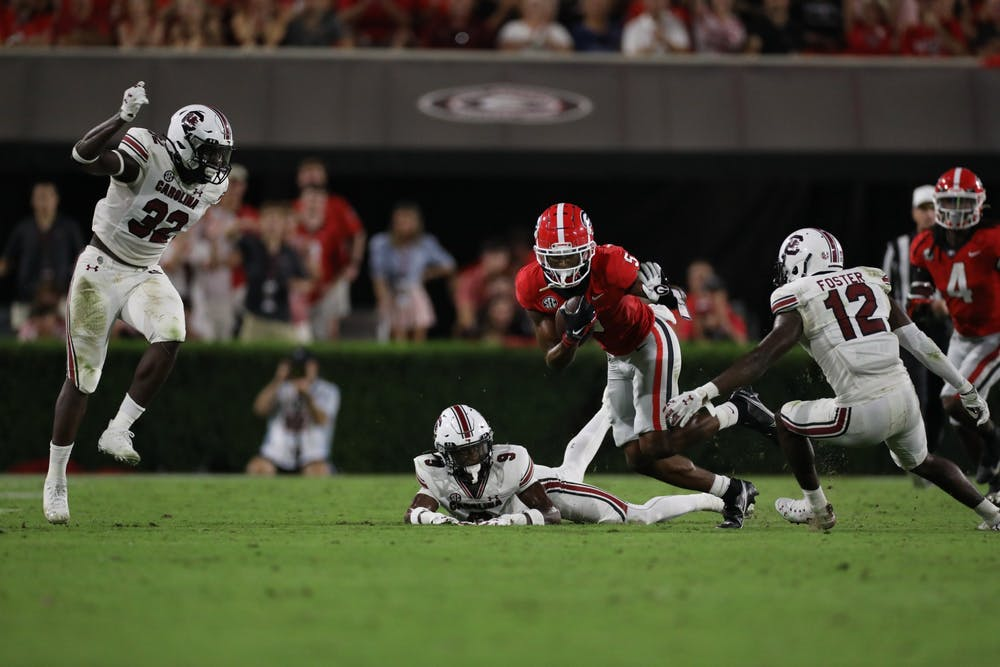 <p>Redshirt sophomore defensive back Cam Smith attempts a tackle on a Bulldogs player. The Gamecocks received their first loss of the season in Saturday's game against UGA.</p>