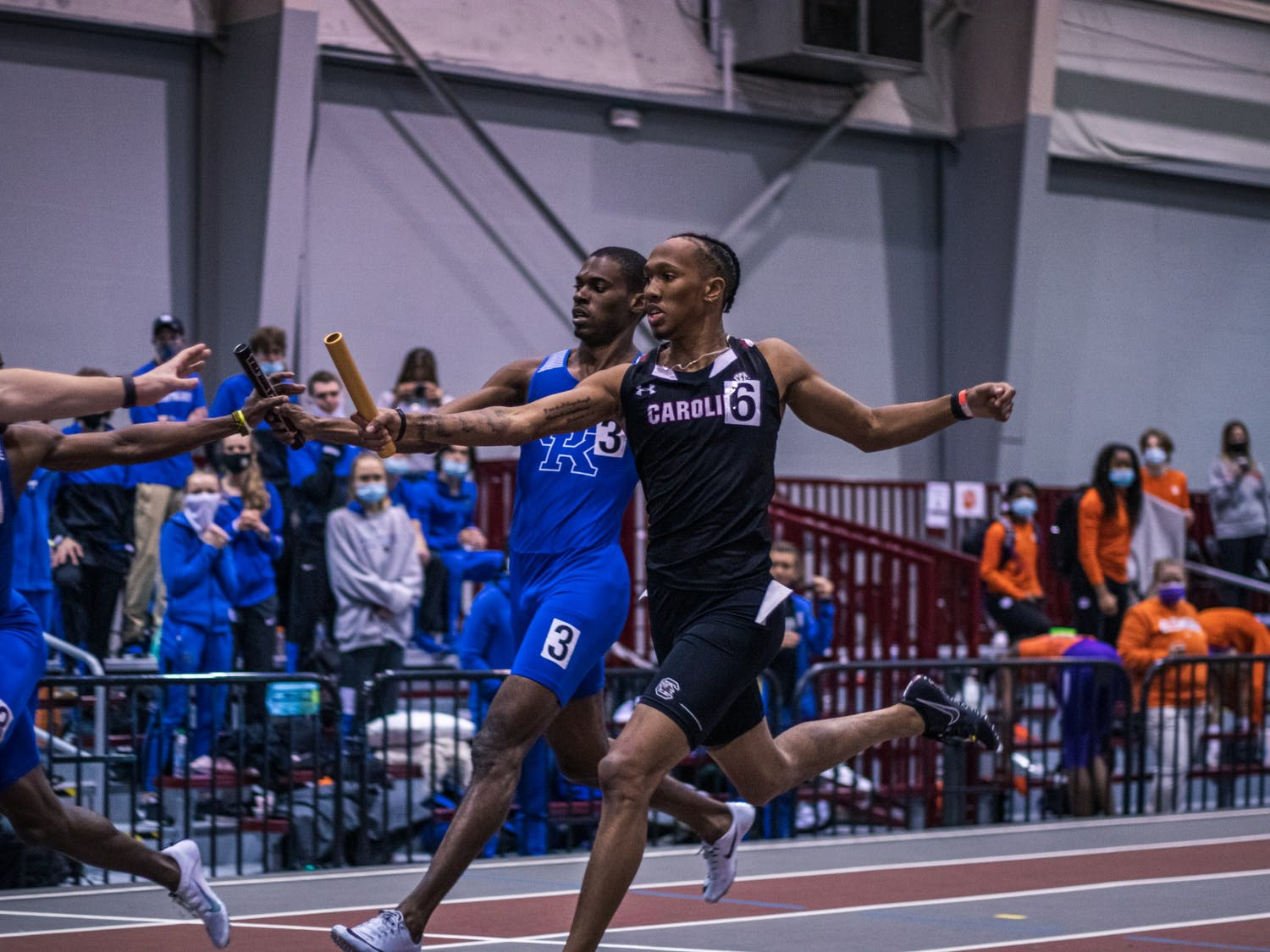 Sophomore EJ Richardson passes the baton to his teammate during a relay race.