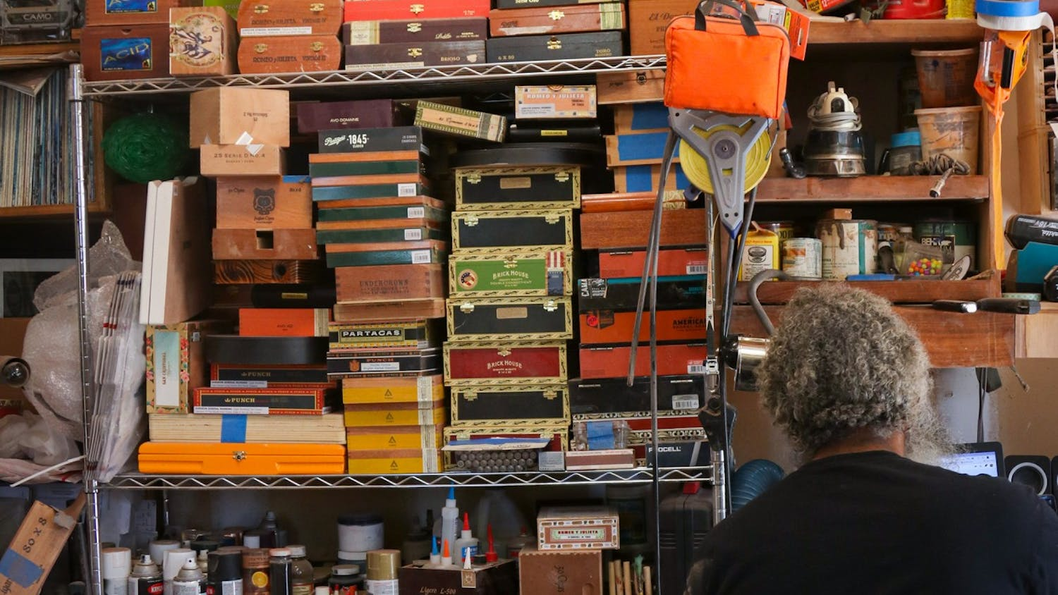 Anthony Walker sits at his computer next to his cigar box shelf in his work garage.