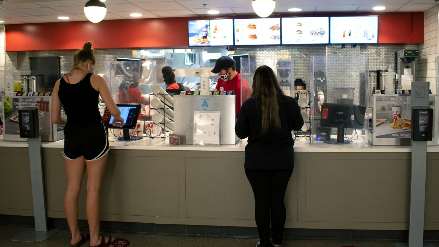Students order at touch screen monitors at the Chick-fil-A in Russell House.