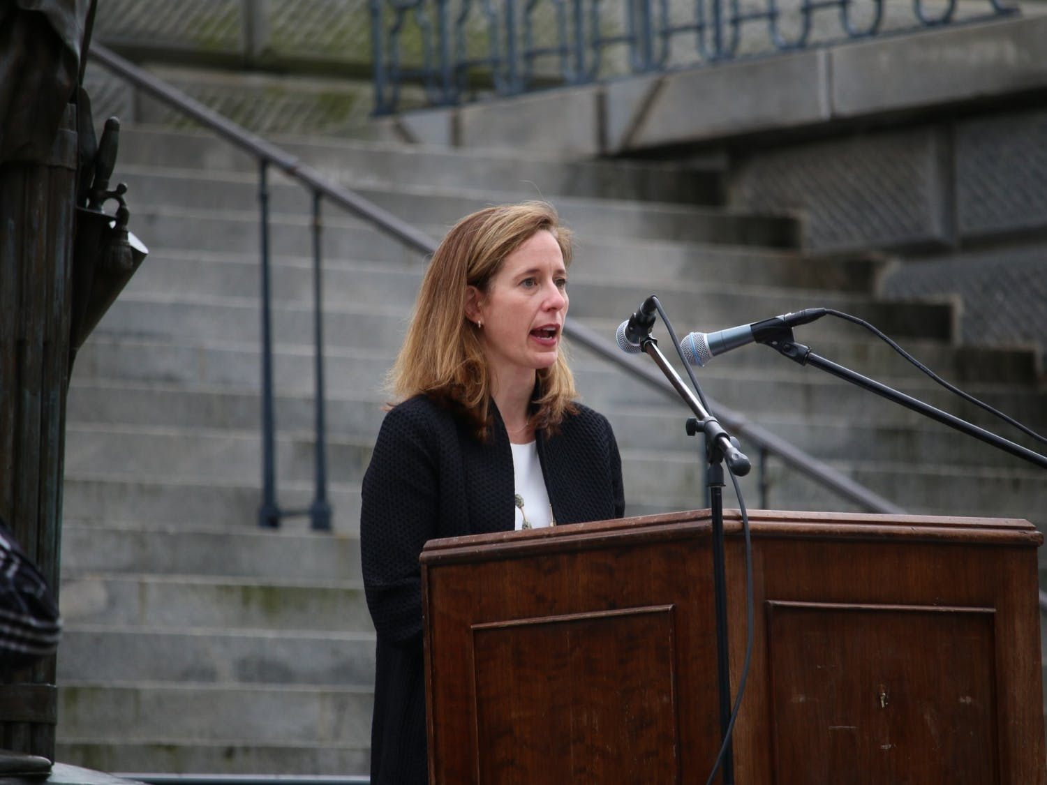 """Ann Warner, CEO of Women's Rights and Empowerment Network (WREN), speaks during Tuesday's protest. WREN was one of the organizations that put together the drive-by """"Stop the Ban"""" protest."""