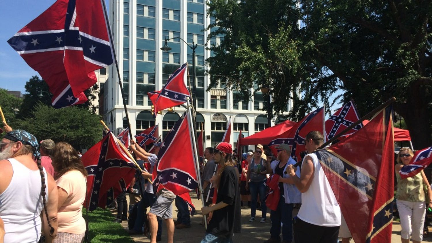 Citizens carry Confederate flags at a rally outside the Statehouseon Sunday, July 10, one year after the flag's removal from Statehouse grounds.
