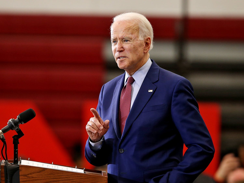 President Joe Biden speaks while standing at a podium.