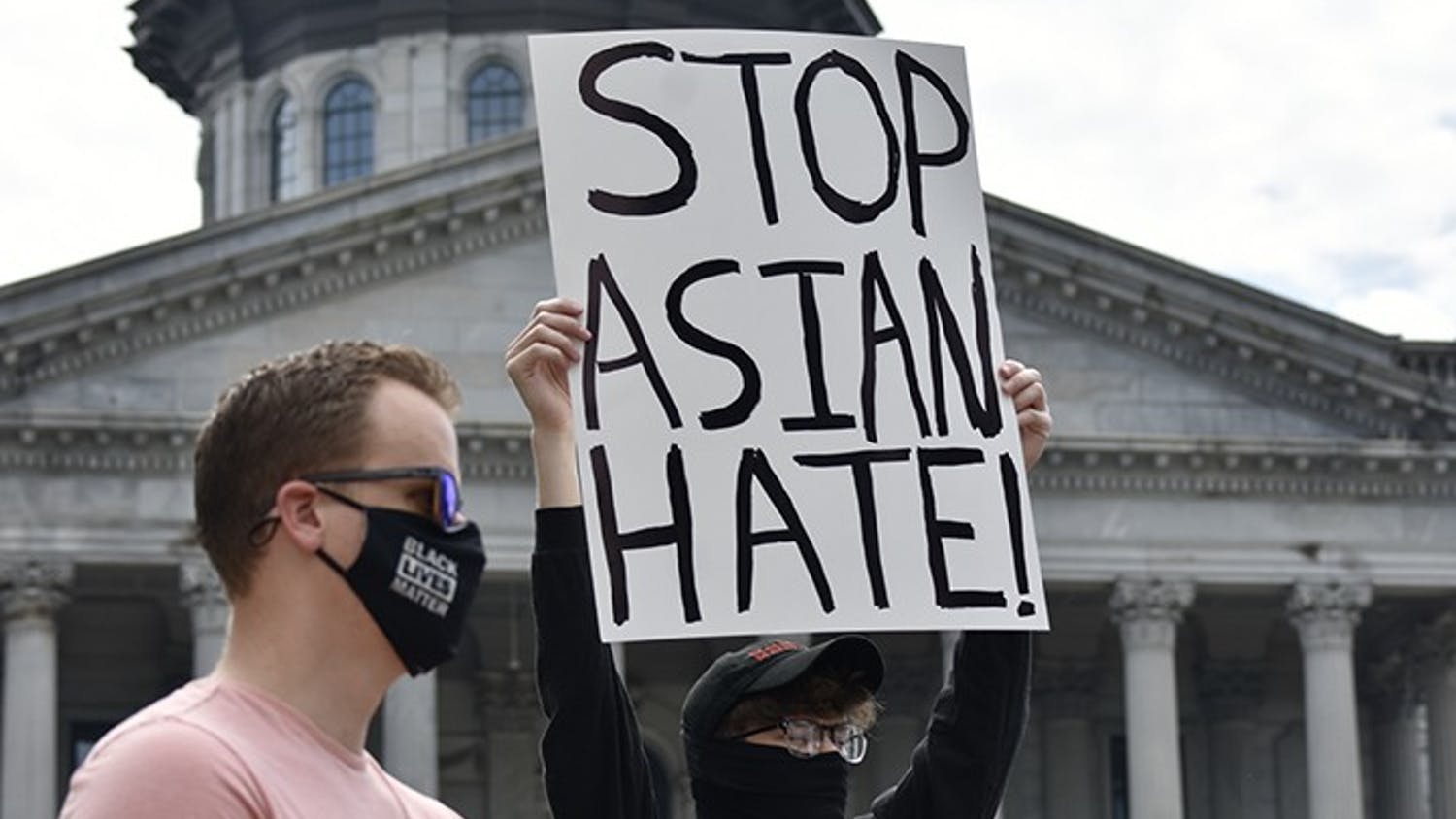 """A protestor displays a sign that reads """"STOP ASIAN HATE"""" in front of the State House on March 7, 2021."""