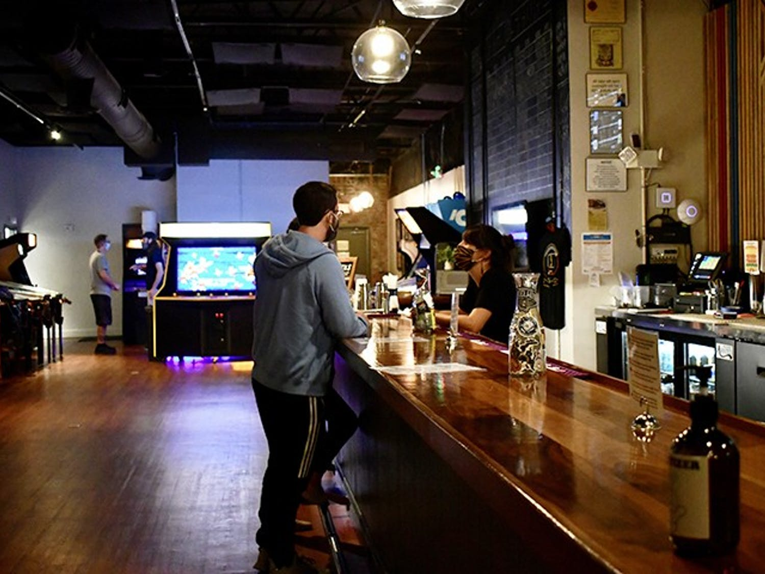 A customer orders from the bar in Transmission Arcade. The arcade is full of retro-themed games and artwork.