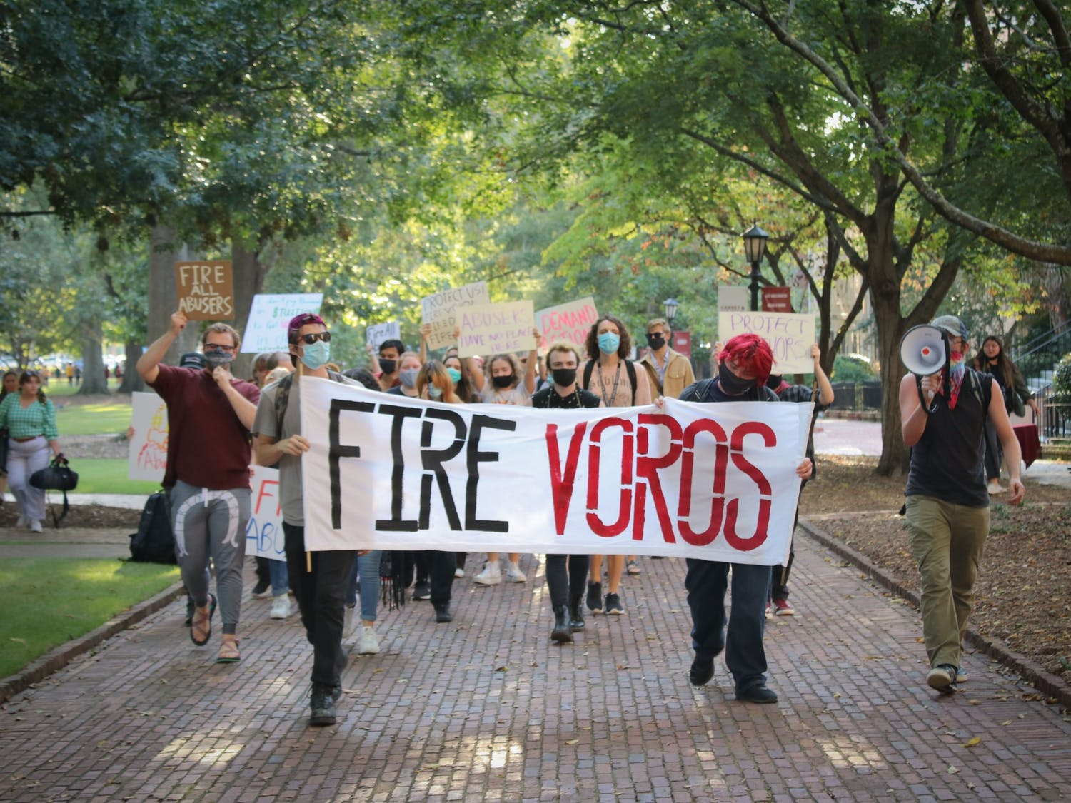Protestors walk down the Horseshoe holding a sign that reads, 'FIRE VOROS.' USC students, faculty and staff protest the university's handling of the sexual assault allegations against professor David Voros and other alleged abusers.