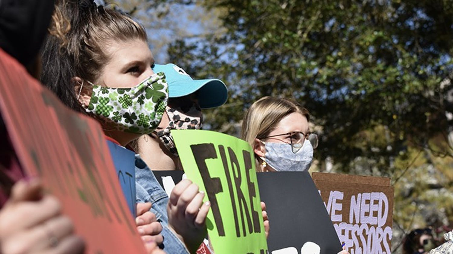 Student protestors hold signs directed towards administrators in the Osborne Administrative Building from the courtyard.