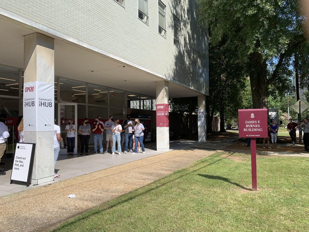 <p>Students working at the new iHub clap as people enter the store. The store opened Aug. 13, 2021, and will service and provide Apple products to the USC community.</p>