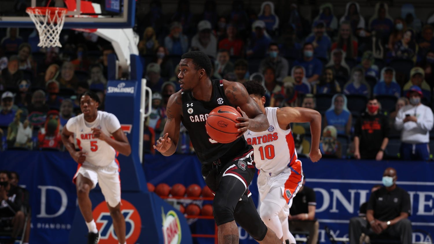 Redshirt sophomore, Jermaine Couisnard, dribbles the ball down the court as a Florida Gators player runs after him. South Carolina won the game 72-66 on Feb. 3, 2021.