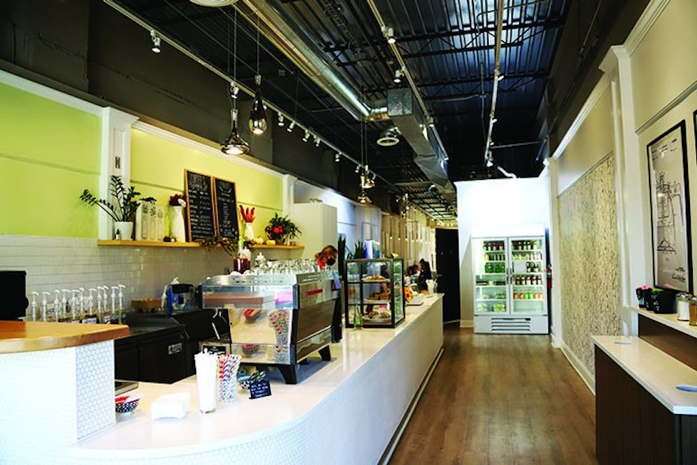 Blum Coffee's bar is brightly lit and located in the front of the store. The bar includes two large chalkboard menus and is lined with coffee machines, syrups and a case of baked goods.