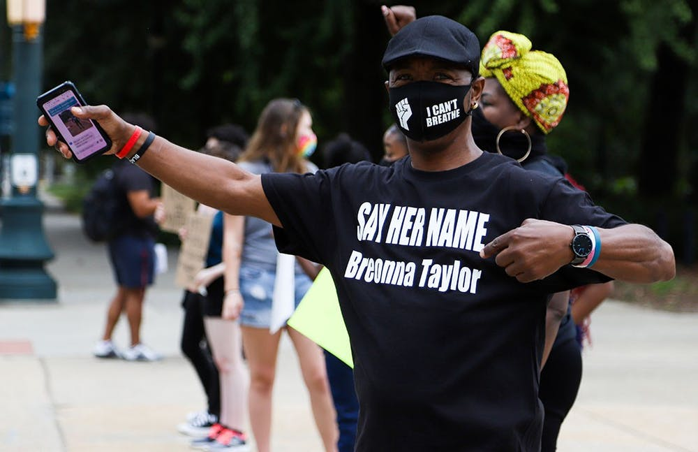 "Protester Clarence Turner stands in front of South Carolina's state capital wearing a T-shirt reading ""SAY HER NAME Breonna Taylor"" and a facemask with the BLM symbol and the phrase ""I Can't Breathe"" in support of George Floyd."