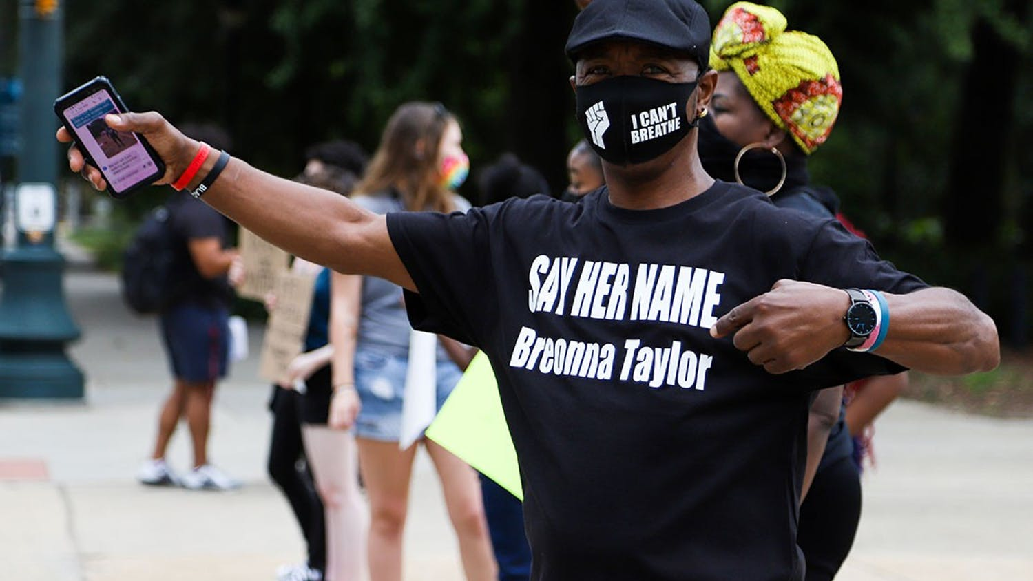 """Protester Clarence Turner stands in front of South Carolina's state capital wearing a T-shirt reading """"SAY HER NAME Breonna Taylor"""" and a facemask with the BLM symbol and the phrase """"I Can't Breathe"""" in support of George Floyd."""