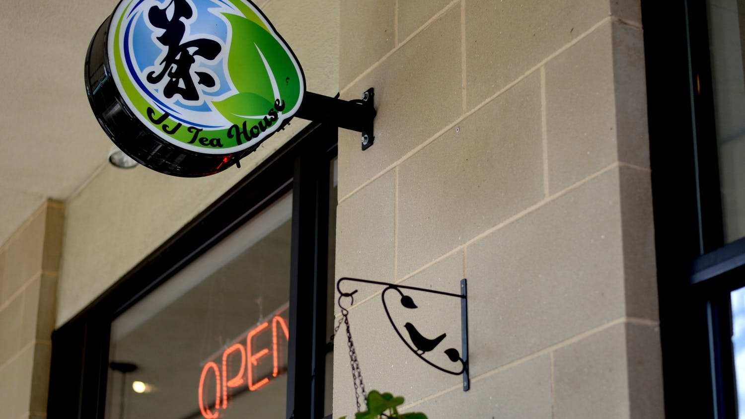 A sign on the front entrance of JJ Tea House welcomes customers.