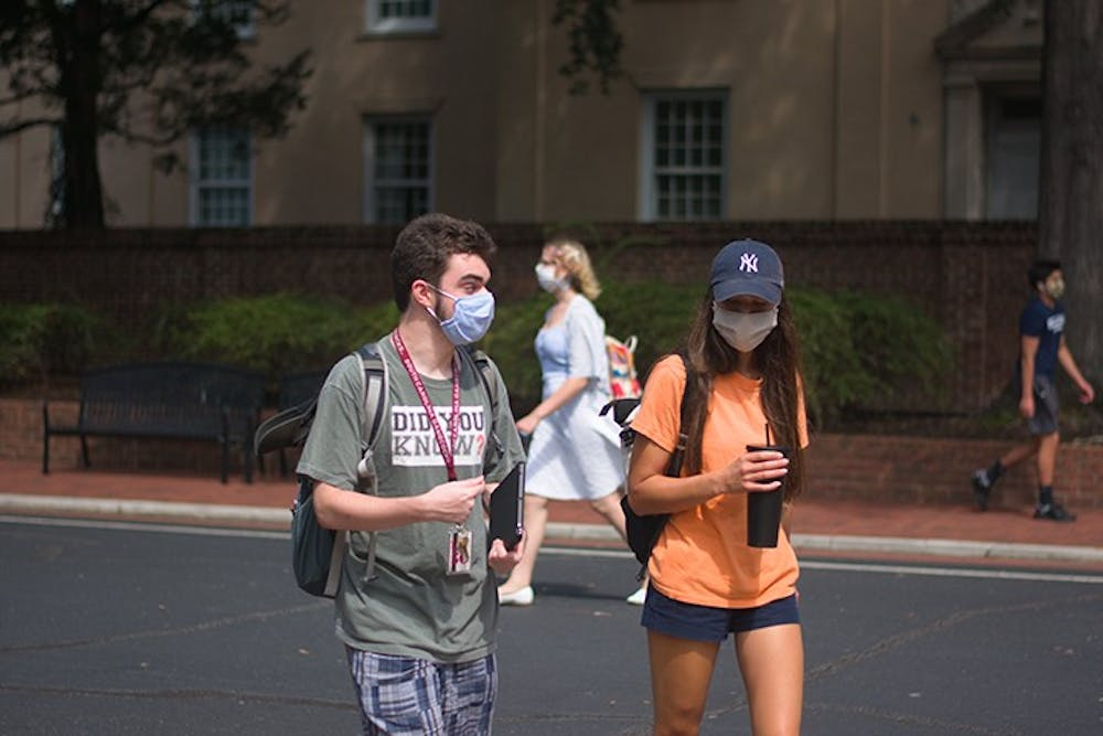 <p>Students walk on campus with masks on. The university has documented over 1,000 student violations related to COVID-19 this semester.</p>