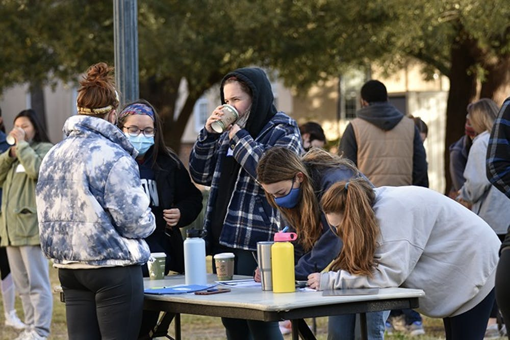<p>Two students signed up for Service Saturday pick their volunteer site. The students then take busses to their respective sites.</p>