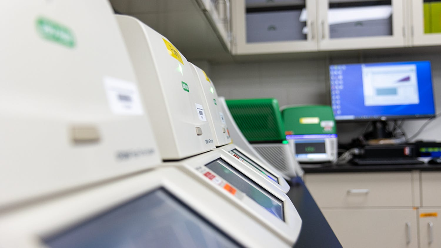 Line of idle Bio-Rad CFX384 PCR detection systems. When in use, these units scan a tray of samples for one hour and 30 minutes before being validated and then uploaded.
