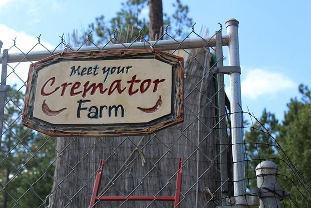 The sign for Meet Your Cremator Farm sits on the front gate. The farm grows peppers that are used to make some of its award-winning hot sauces.