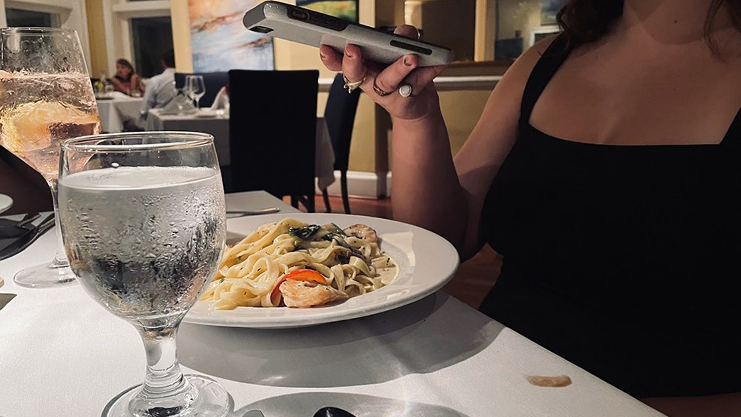 A person uses their phone to get a snapshot of their dinner served at a restaurant.