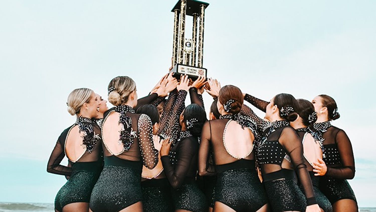 The Carolina Girls dance team posing with the National Championship trophy.