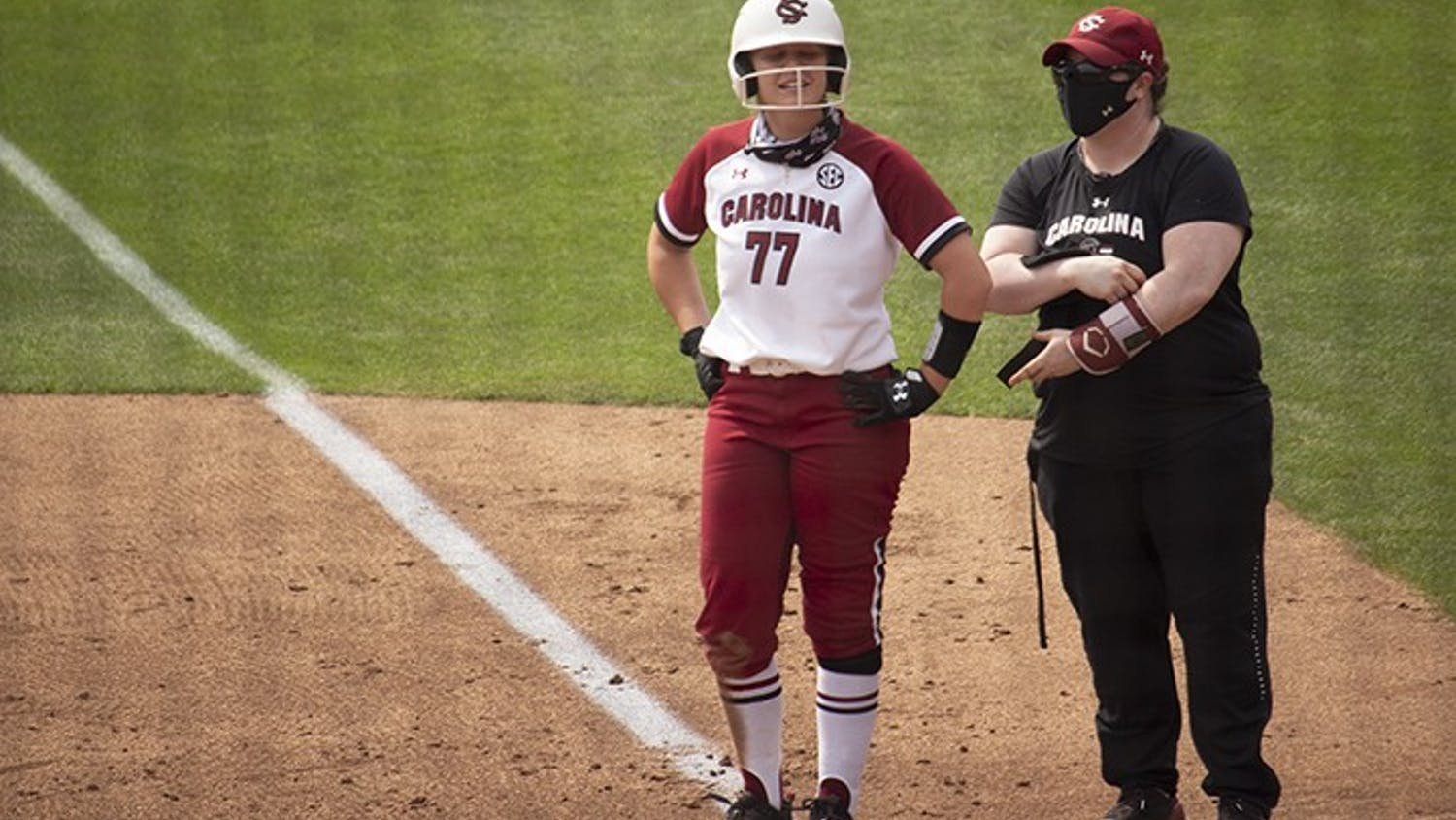 Junior infielder Kassidy Krupit stands at first base talking to one of her coaches.