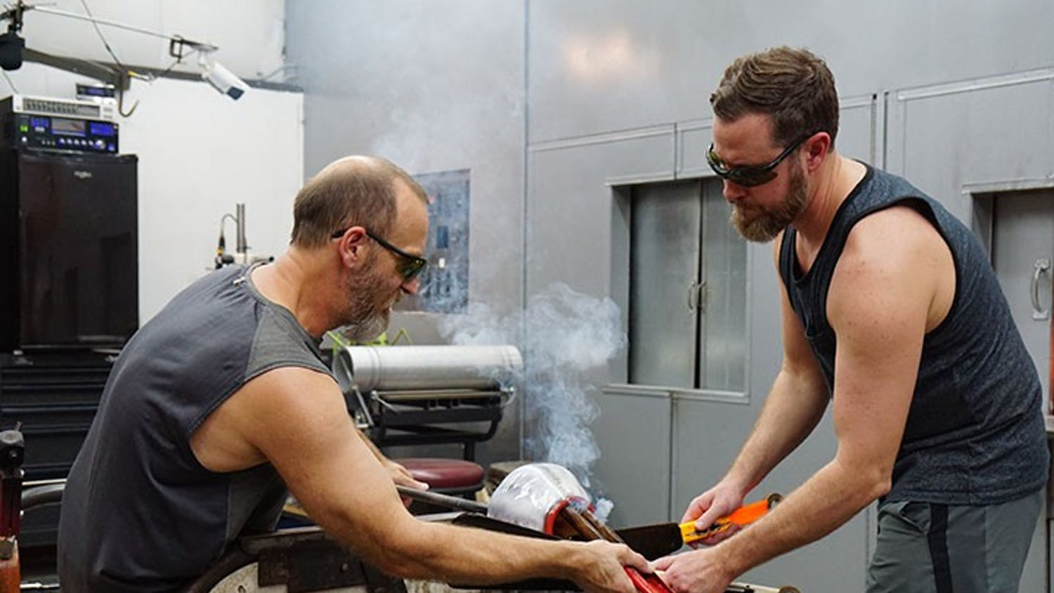 "Tom Lockart and Ryan Crabtree open the top of their molded glass to prepare it to be flattened into a plate while smoke rises. The duo could be heard listening to a playlist of '90s rock while they worked, including the Red Hot Chili Peppers' ""Higher Ground."""