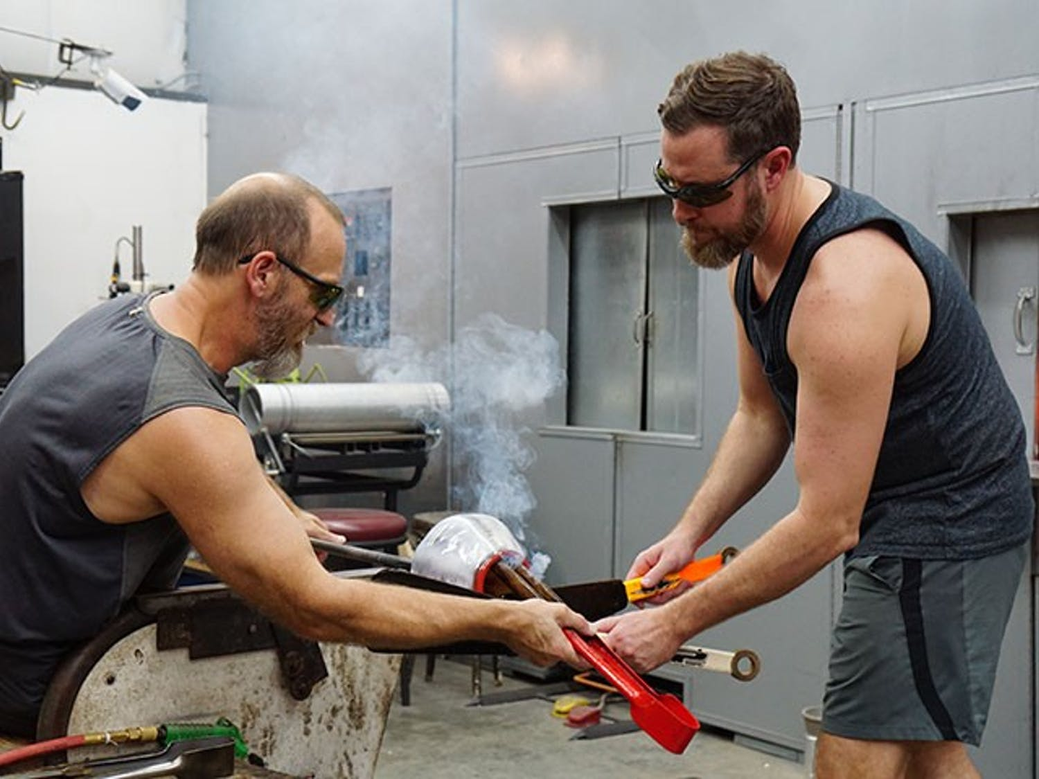 """Tom Lockart and Ryan Crabtree open the top of their molded glass to prepare it to be flattened into a plate while smoke rises. The duo could be heard listening to a playlist of '90s rock while they worked, including the Red Hot Chili Peppers' """"Higher Ground."""""""