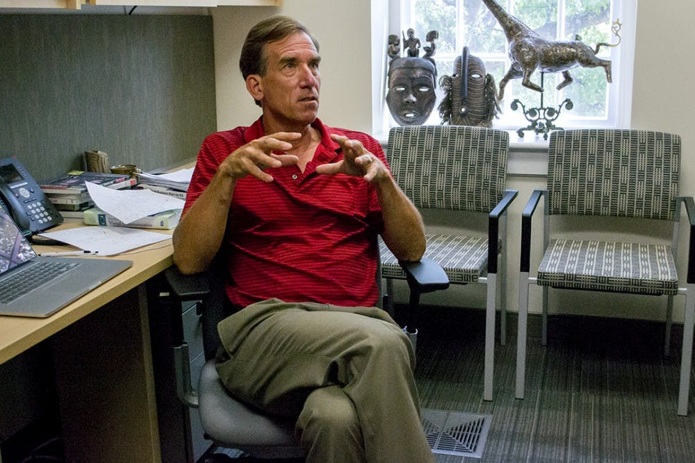 <p>Keith Kenney displays a ceramic piece by his wife and authentic African art in his office in the journalism school.</p>