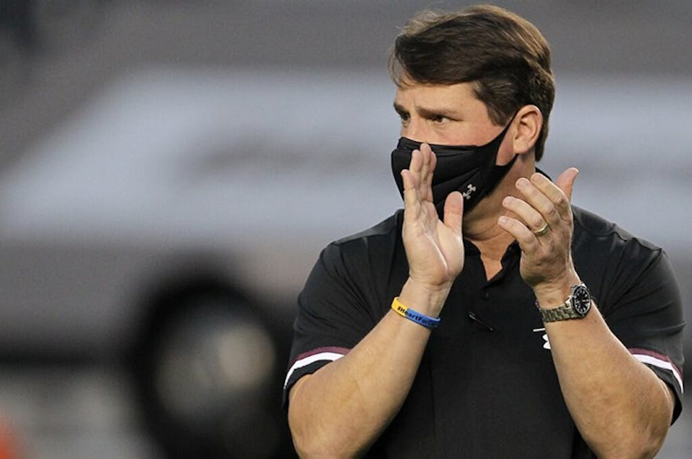 University of South Carolina football head coach Will Muschamp claps while walking down the sideline of the football game against the Tennessee Volunteers.