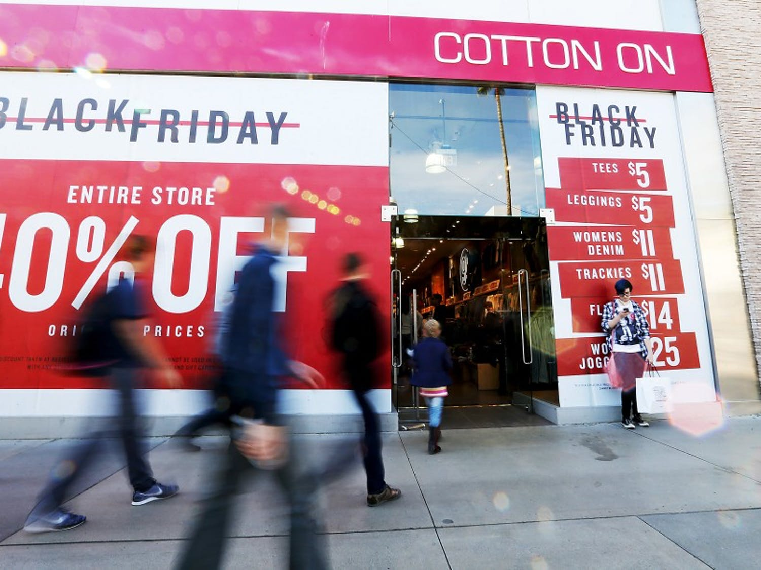 Shoppers flock to a store advertising steep discounts along the Third Street Promenade in Santa Monica, Calif., on Friday, Nov. 27, 2015. (Luis Sinco/Los Angeles Times/TNS)