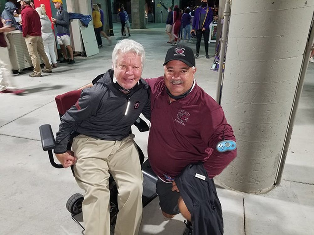 Kirk Hollingsworth (left) and Chris Fulmer (right) take a picture together at a Gamecock football game. The duo have been attending games religiously since they were kids.