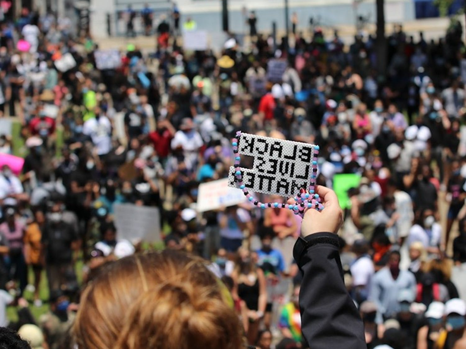 """A protestor holds a handmade Perler bead design that reads 'BLACK LIVES MATTER.' Protestors filled the steps of the capital and the grounds below chanting """"No justice, no peace."""""""