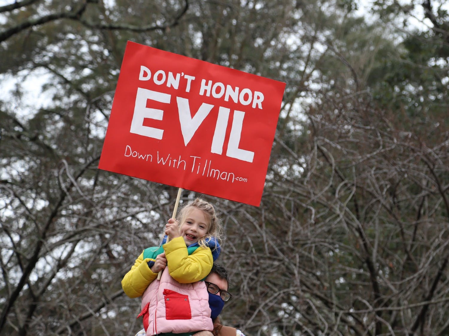 """A protestor holds up a child with a sign saying """"DON'T HONOR EVIL, Down with Tillman"""" in front of the Benjamin Tillman statue on Tuesday January 12, 2021."""