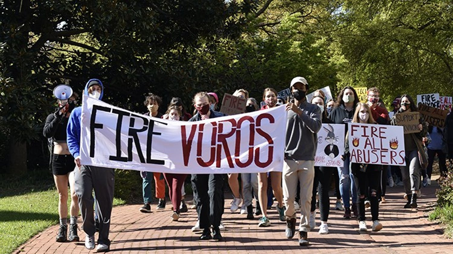 Protestors march from Pickens Street Bridge to the President's House holding signs that demand the firing of all professors accused of sexual misconduct.