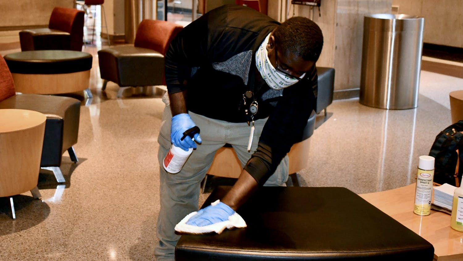A member of the USC custodial staff cleans a seat in Russell House.