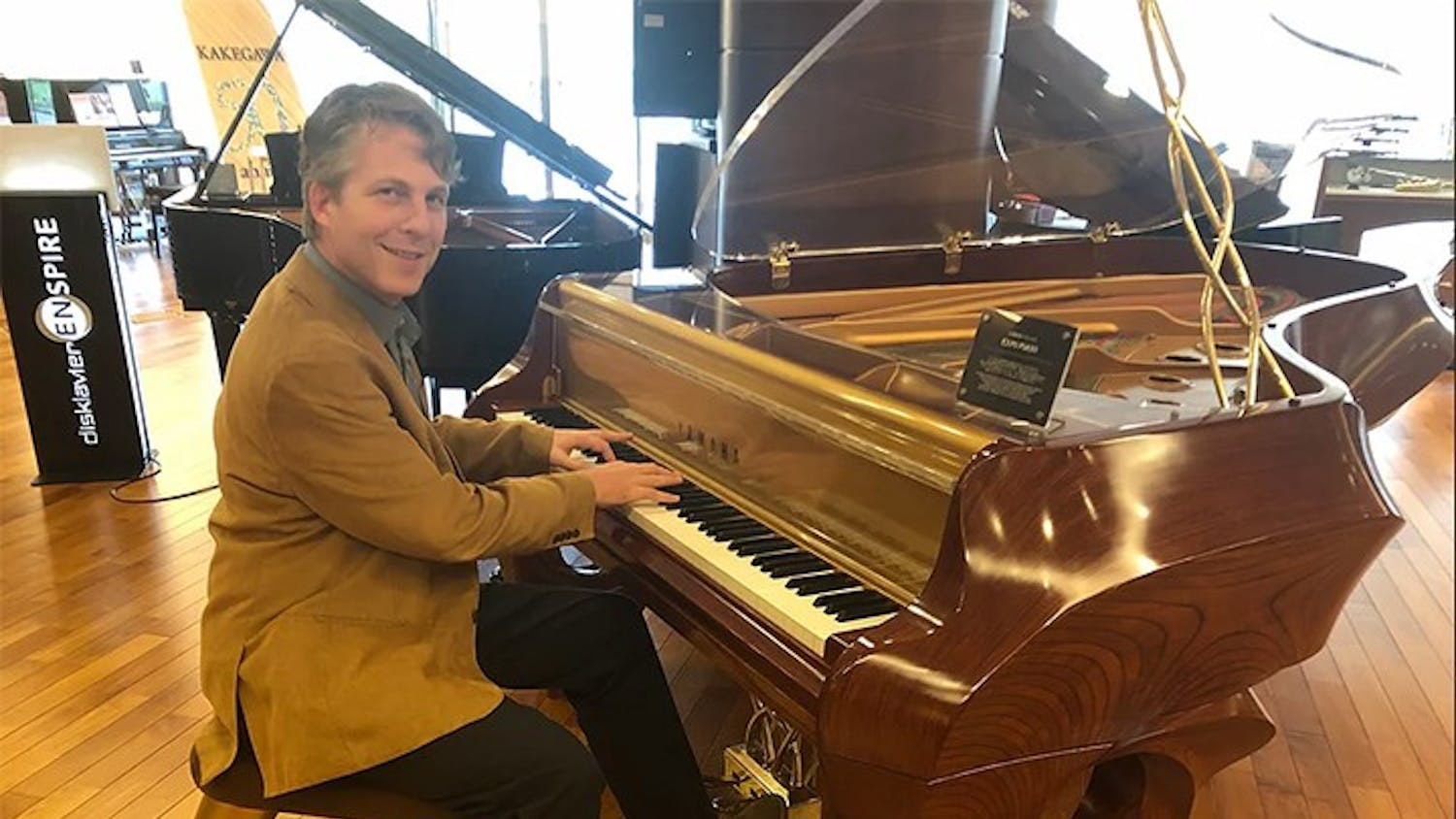 """Music entrepreneurship professor David Cutler, whose book """"The Savvy Musician"""" focuses on how to turn a musical education into a successful career, poses with a piano."""